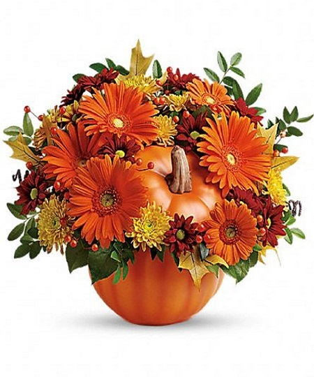 halloween glow features yellow chrysanthemums orange roses eucalyptus and autumn leaves in an orange cube vase that features a jack o lantern face